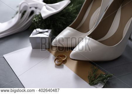 Composition With Wedding Rings, White High Heel Shoes And Decor On Grey Background