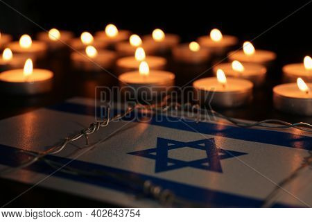Flag Of Israel, Barbed Wire And Burning Candles On Black Background. Holocaust Memory Day