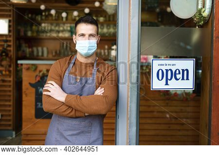 Portrait Of Smiling Owner Man Wearing Face Mask For Prevention While Standing At His Cafe Door With