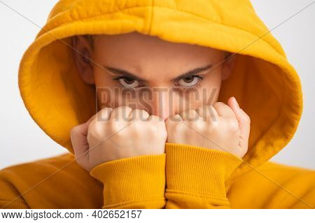Young Woman In Ocher Hood Holding Fists Near Face On White Background.