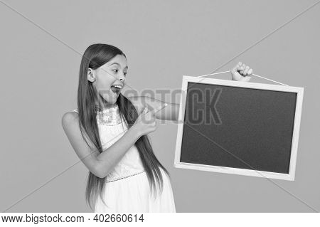 Happy Smiling Girl Hold Blackboard. Small Kid With Blank Blackboard. Advertisement Promotion Copy Sp