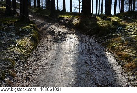 Snowy Road. The Stones Protruding From The Surface Of The Road Are The Remains And Foundations Of A