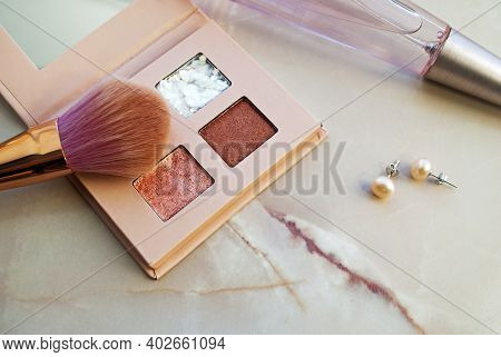 Eyeshadow Palettes In Pink With A Gold Brush, Perfume And Pearl Earrings. Cosmetic Branding, Girly A