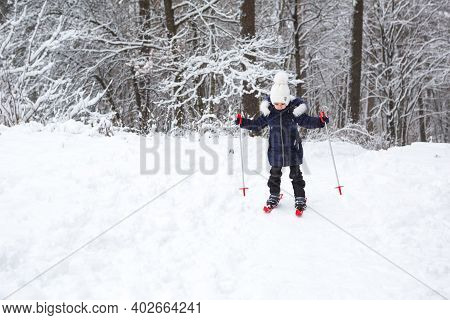 Children's Feet In Red Plastic Skis With Sticks Go Through The Snow From A Slide-a Winter Sport, Fam
