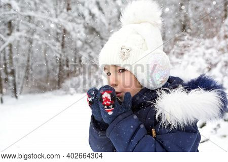 A Little Girl In The Cold Warms Her Hands In Mittens-breathes Warm Air From Her Mouth On Her Hands.