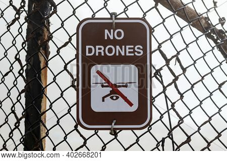 No drones warning sign on old rusty fence.