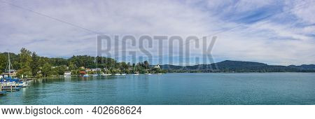 Boats On The Clear Waters Of Alpine Lake Worthersee, Famous Tourist Attraction For Many Water Activi