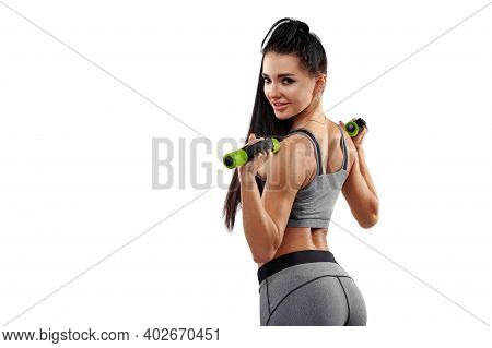 Beautiful Muscular Buildwoman Smiling From Behind Holds Dumbbells And Strains Her Back Muscles And T