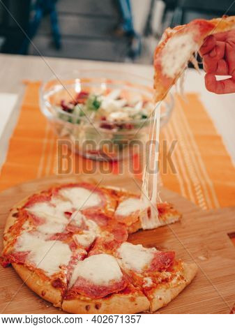 Woman Hand Takes A Slice Of Sliced Pizza With Mozzarella Cheese, Tomatoes, Pepper, Olive, . Italian