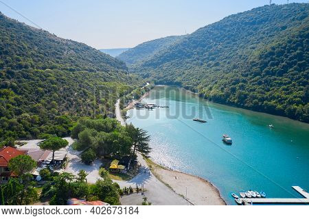 Forested Mountainous Area With A Narrow Reservoir. On The Shore Of The Reservoir There Are Houses Wi