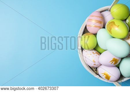 Easter Basket Filled With Painted Easter Eggs Over A Blue Background. Colorful Painted Easter Eggs I