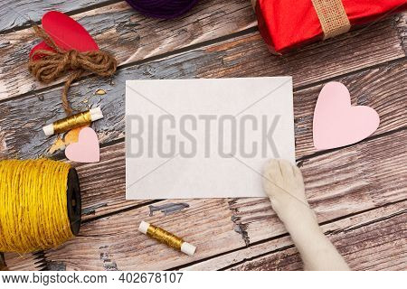 Blank Card Held By Pet Hand. Table With Craft Items. Valentines Day Card.