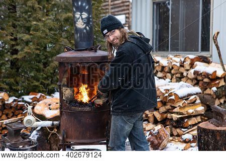Young Long Haired Man Playing With A Forge And Pretending To Be The Blacksmiths Apprentice. Outdoor