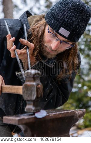 Close Up Shot Of A Young Blacksmith Under The Snow, Concentrated In Hammering And Flattening A Red,