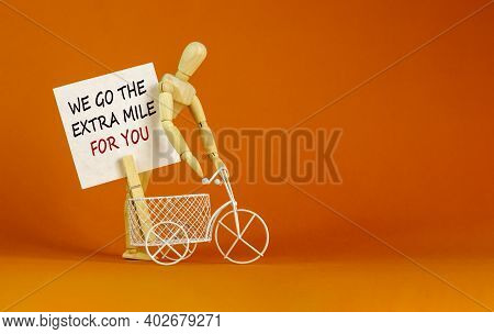 Go Extra Mile Symbol. White Sheet Of Paper. Words 'we Go The Extra Mile For You'. Miniature Bicycle
