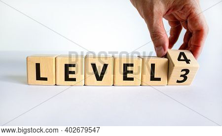 Time For Level 4. Hand Turns A Cube And Changes Words 'level 3' To 'level 4'. Beautiful White Backgr