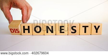 Honesty Or Dishonesty Symbol. Businessman Hand Turns Cubes And Changes The Word 'dishonesty' To 'hon