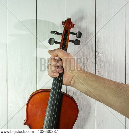 A Violin Instrument In The Hand With A White Wooden Background