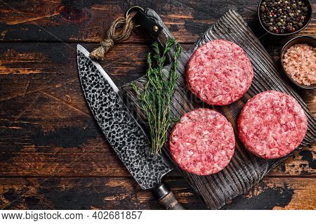 Raw Steak Burgers Patties With Ground Beef And Thyme On A Wooden Cutting Board. Dark Wooden Backgrou