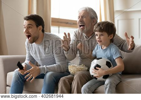 Three Generations Of Men Watch Football At Home