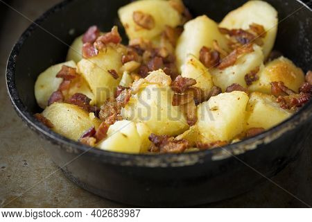 Close Up Of A Pan Of Rustic Baked Potatoes And Bacon