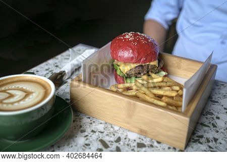 Man Sitting At A Table With Burger, Potato Chips And Coffee. Meal Time Concept.