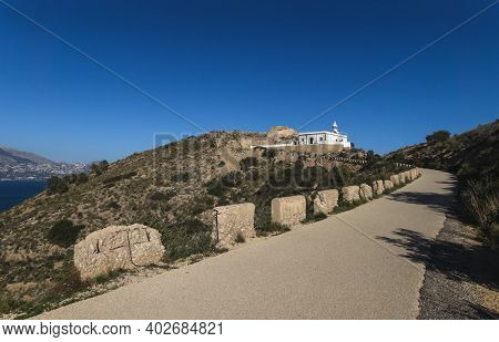 Sunny Walking Path In The Natural Park Serra Gelada Towards The White Lighthouse On The Cliff, Albir