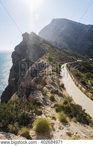 Man On Scenic Walking Path Along Steep Cliffs Along The Ocean In The Natural Park Serra Gelada In Al