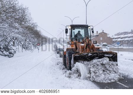 A Snow Removal Machine Removes The Snow From A Street In A Residential Area, Two Cars Drive Behind I