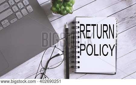Return Policy Text Written On Notebook With Pencils, Magnifier And Alarm Clock