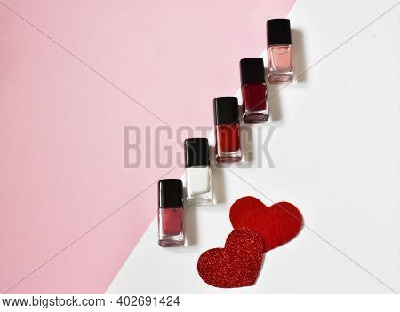 Nail Polishes And Hearts On Pink Background. Valentines Day, Mother's Day Or Women's Day. Women's Be