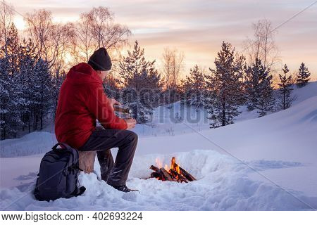 Man Traveler Holding Thermos Bottle And Cup Of Tea, Sitting Near The Fire In Winter Forest. Adventur