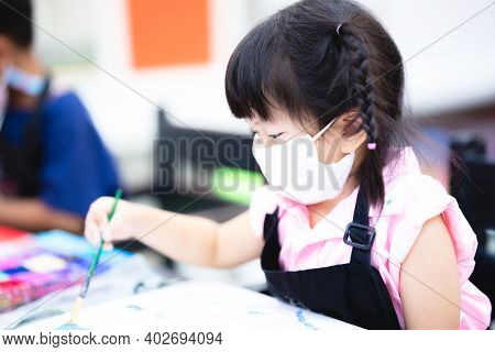 Pupils Girl Wearing Mask Are Concentrating On Drawing And Painting With Brush And Watercolor On The