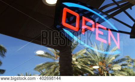 Open Neon Sign Glowing In The Dark. Vivid Retro Styled Text At Entrance On Glass Window. Colorful El
