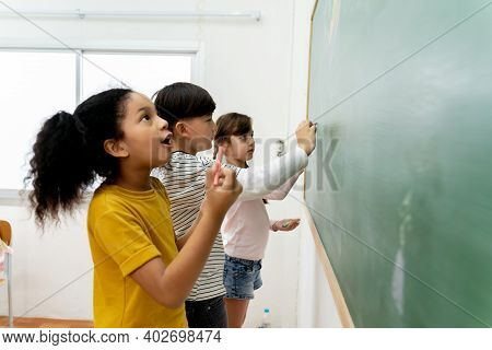 Side View Of Amazed Black Girl Drawing On Chalkboard Near Multiracial Classmates During Lesson At Pr
