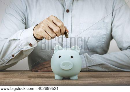 Businessman Save Money On Piggy Bank , Hand Put Money Coin Into Piggy Bank For Save