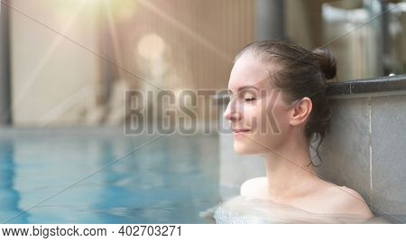 Wellness - happy white woman in her 30s relaxing in wellness resort pool, smiling.