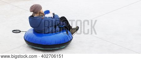 Family Having Fun On Snow Tube. Mother With A Kid Is Riding A Tubing. Winter Entertainment. People S
