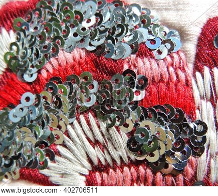 Macro Texture Embroidery Pink Red White Thread And Silver Sequins On Fabric. Colorful Embroidery Ove