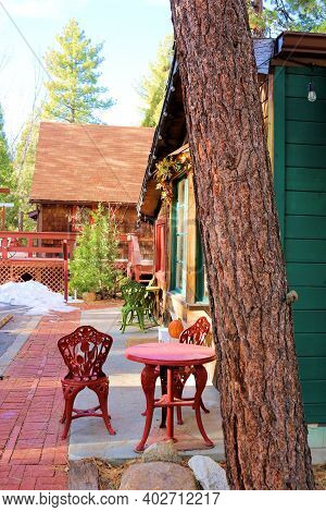 Rustic Building With Retail Stores Including Outdoor Patio Furniture Surrounded By Pine Trees Taken