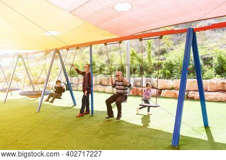 Multi-generational Happy Family Spends Time Together One Sunny Day In The Playground. Joyous Active