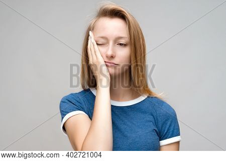 Photo Of Tired Young Female With Blond Hair, Covers Face, Feels Fatigue, Needs Good Rest, Dressed In