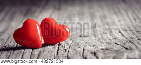 Two red heart on a wooden background concept for love, dating and romance with copy space