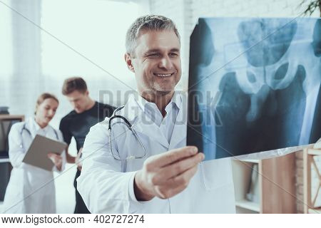 Male And Female Doctors With Stethoscopes In Office. Doctor Is Looking At X-ray.