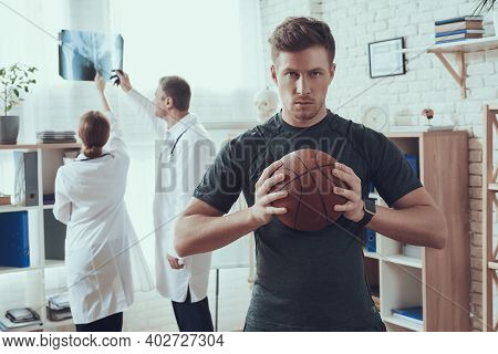 Male And Female Doctors With Stethoscopes In Office. Basketball Player In Hospital.