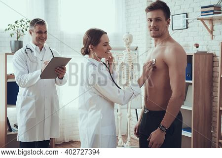 Male And Female Doctors With Stethoscopes In Office. Doctor Is Listening To Heart With Stethoscope.