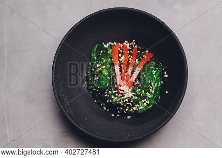 Close-up Of Chuka Salad Served In A White Bowl, Vertical Shot, Dark Brown Stone Background.