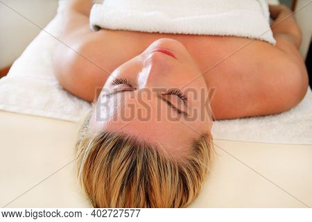 Woman On Massage Table, Closeup Face. Portrait Of Relaxed Handsome Pretty Young Girl Enjoys And Layi
