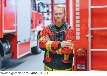 Determined young fire fighter in front of a fire truck in the warden