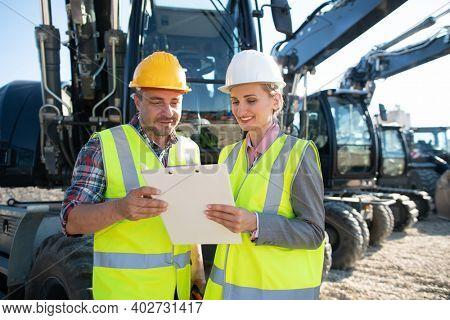 Two workers in open cast mine standing in front of heavy machinery with clipboard discussing